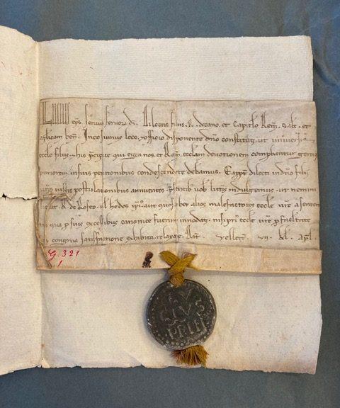 Source : Archives départementales de la Marne (AD 51), Reims, 2G 321/1 (cliché personnel).   Petite bulle du pape datée de 1182/1182 et reconnaissable à son sceau en plomb très bien conservé.